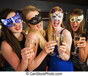 Attractive friends with masks on holding champagne glasses...