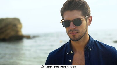 Attractive funny young man in fancy sunglasses, smiling and posing on the camera.