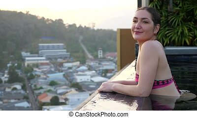 happy girl enjoys pictorial landscape standing in hotel swimming pool in summer evening closeup