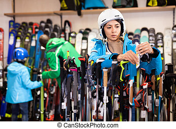 Attractive girl choosing ski poles for skiing in store of sports equipment