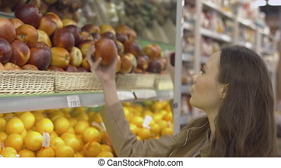 Attractive girl comes to the showcase with fruits and picks apples at the supermarket