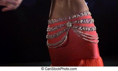 Attractive girl dancing belly dance on black, back light