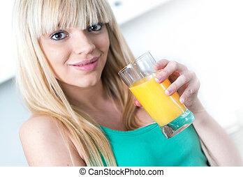 Attractive girl drinking an orange in a kitchen