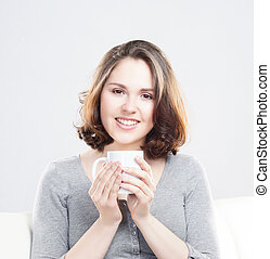 Attractive girl enjoying a cup of coffee at home