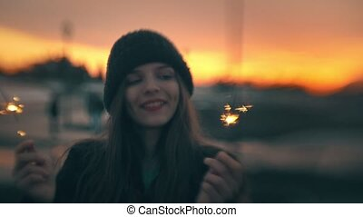 Attractive girl having fun with sparkler at sunset outdoors
