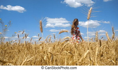 attractive girl in a bright dress standing in a wheat field in the wind