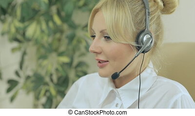 Attractive girl in business clothes sitting with headphones and speak into the microphone