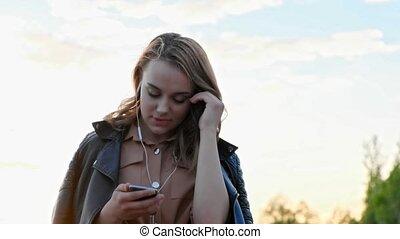 Attractive girl in headphones using smartphone, listening to...