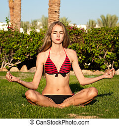 Attractive girl in one of the yoga postures close up