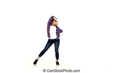 Attractive girl in plaid shirt dancing lady style and turns on white background