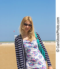 Attractive girl in sunglasses on the beach spring