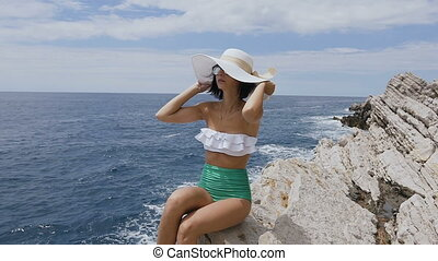 Attractive girl in sunglasses sits on the rock, in a bathing suit, wears hat on the background of sea blue water. Adriatic sea, Budva, Montenegro