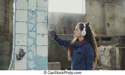 Attractive girl is concentrated on decorating old dirty...