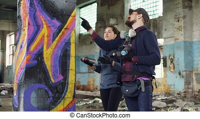 Attractive girl is learning how to create graffiti under...