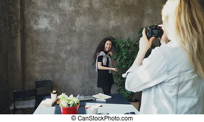 Attractive girl is posing with large plant while female colleague photogrpahing her on digital camera in modern lof office. Women are having fun and laughing during coffee break