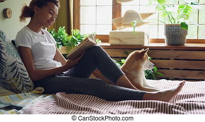 Attractive girl is reading book and stroking beautiful dog...
