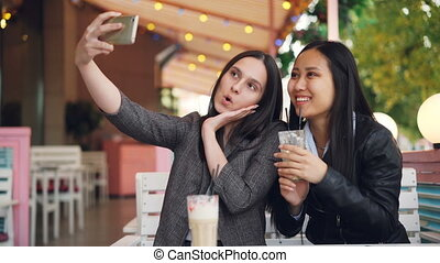 Attractive girl is taking selfie with her Asian friend sitting in open-air cafe with drinks holding smartphone and posing with glasses. Friendship, technology and leisure concept.