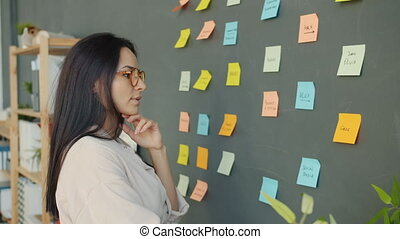 Attractive girl looking at bright sticky notes on wall and ...