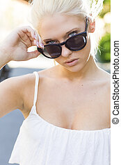 Attractive girl looking over her sunglasses
