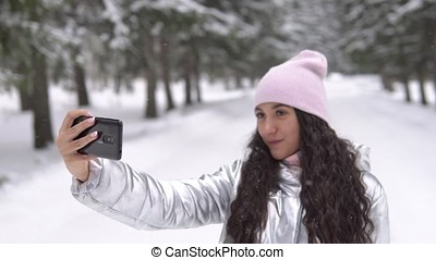 Attractive girl makes selfie using a smartphone while standing in a winter forest. 4K