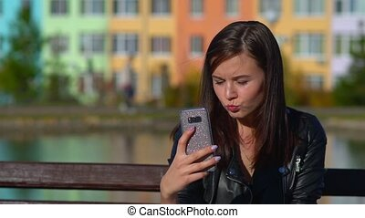 Attractive girl on the street takes a selfie on your smartphone.