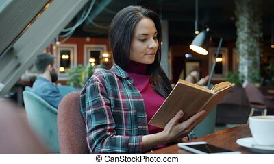 Attractive girl is reading interesting book in cafe relaxing sitting at table alone turning page concentrated on activity. Modern lifestyle and literature concept.