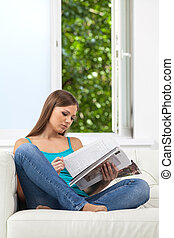 Attractive girl reading magazine on sofa. girl holding magazine at home next to open window