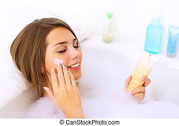 Attractive girl relaxing in her bathtub