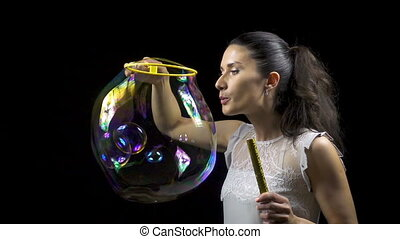 Attractive girl releasing soap bubbles on black background