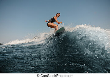 Attractive girl riding on the wakeboard on the clear lake
