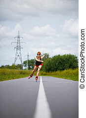 Attractive girl rollerblading on the road - Attractive young...