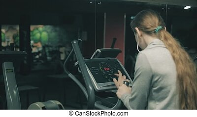 Attractive girl running on a treadmill in the gym 4k