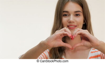 Attractive girl showing heart shape gesture - Brown-haired...