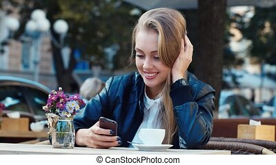 Attractive girl sitting in a cafe writing sms