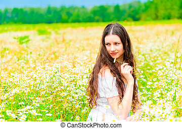 Attractive girl sitting in a field of daisies and looking away