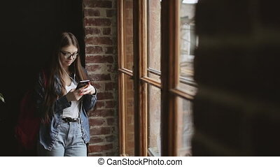 Attractive Girl Standing by Window and Texting - Young girl...