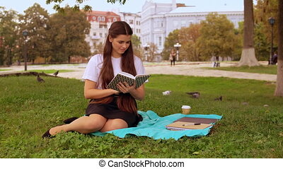 attractive girl studying outdoors - Young caucasian brunette...