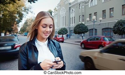 Attractive girl walking down the street and writing sms