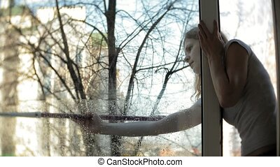 attractive girl washes windows at home. To clean up the...