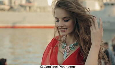Attractive girl with big blue eyes wearing a red dress walking near the sea