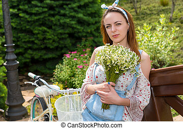 Attractive girl with flowers standing near bike