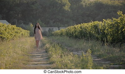 Attractive girl with long black hair walk between the rows of the vineyard