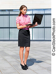 Attractive girl with notebook in front of office building