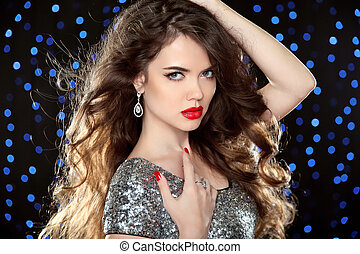 Attractive girl with red lips. Glamour portrait of beautiful woman model in red with professional makeup and romantic wavy hairstyle around the blue lights on dark holiday