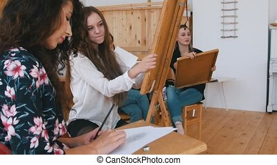 Attractive girls are sitting behind the easel close up -...