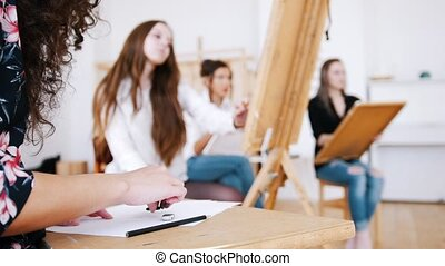 Attractive girls are sitting behind the easel close up hands...