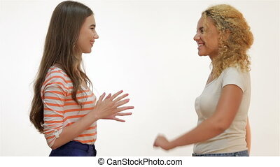 Attractive girls talk to each other and clap palms - Two...