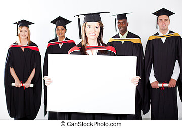 attractive graduate holding white board with classmates in...