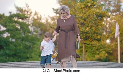Attractive grandmother and grandchild holding hands walking...