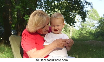 Attractive grandmother with her grandchild having fun in summer park
